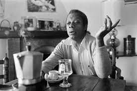 A black and white photo shows James Baldwin sits at a table gesturing with one hand with a coffee pot and glasses in front of him.