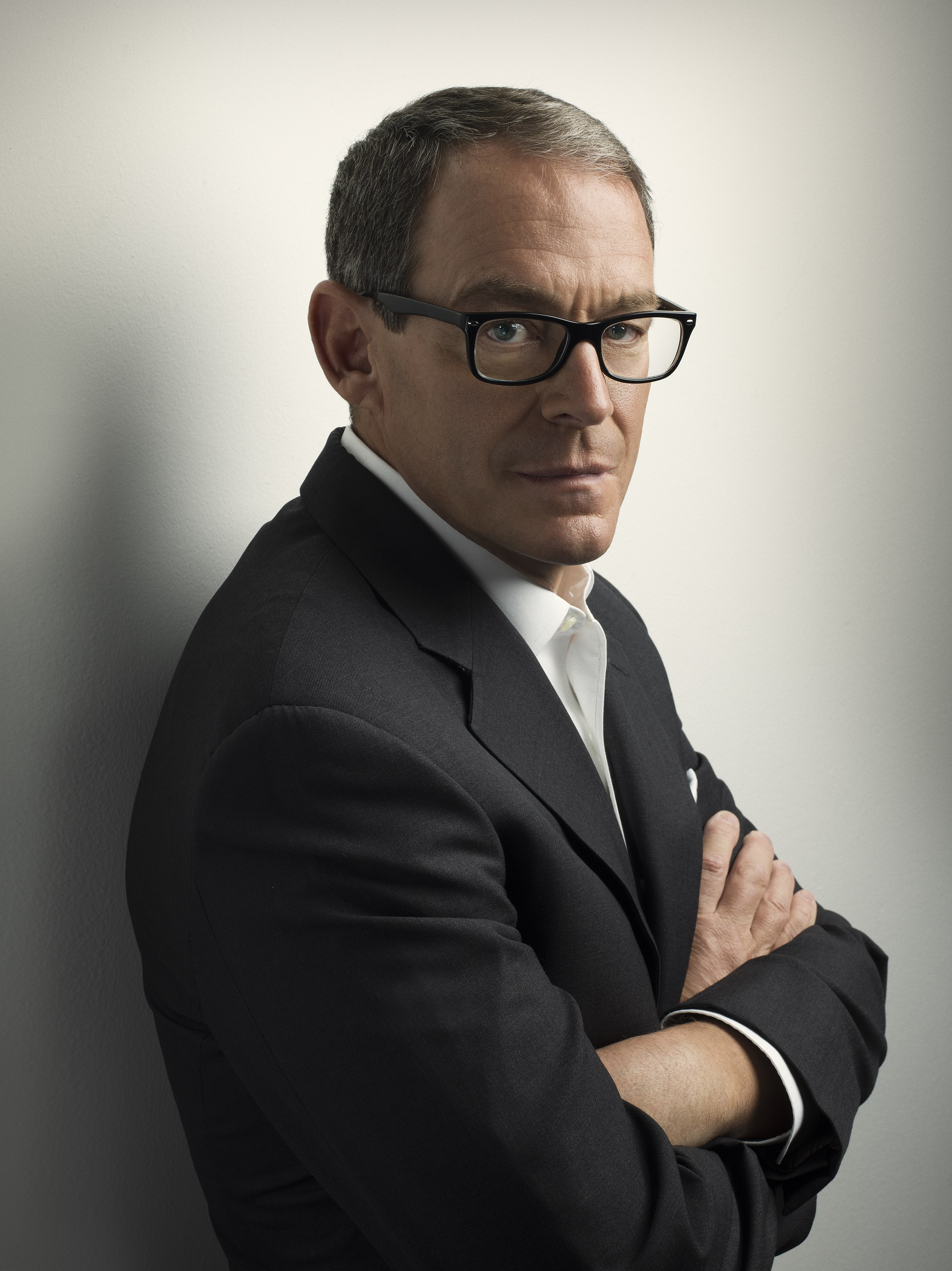 Photo credit: Marco Grob. Author wears a dark jacket, a white shirt, and black framed glasses. He leans against a wall with his arms folded