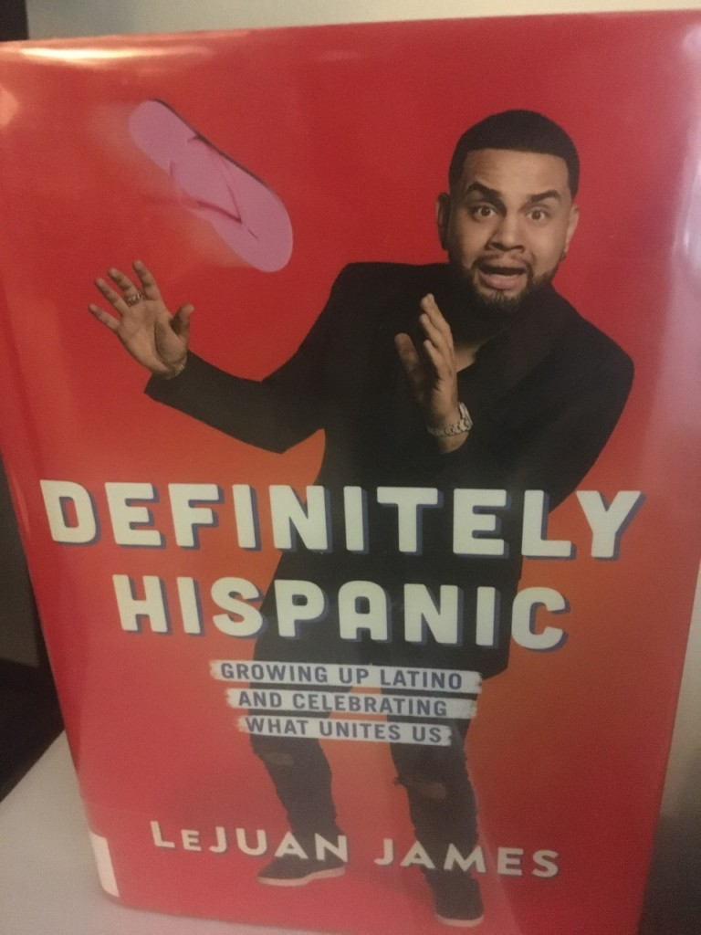 The book cover shows the author in a black suit and sneakers with a startled expression on his face, about to catch a pink flip-flop that is flying towards him through the air. He is posed against a red background.