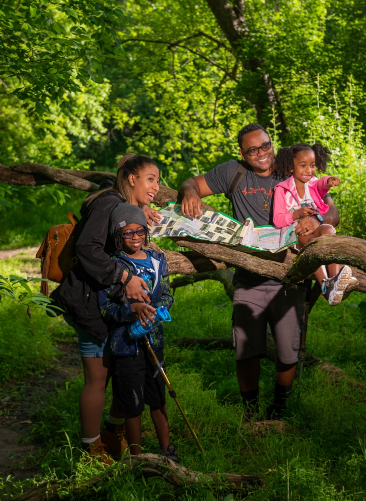 A family stands in a local park with a map spread out along a low horizontal tree branch.