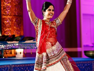 An Indian woman wearing an elaborate red and multi-colored embroidered dress raises her arms, with her hands flexed above he head. Background is purple and blue.