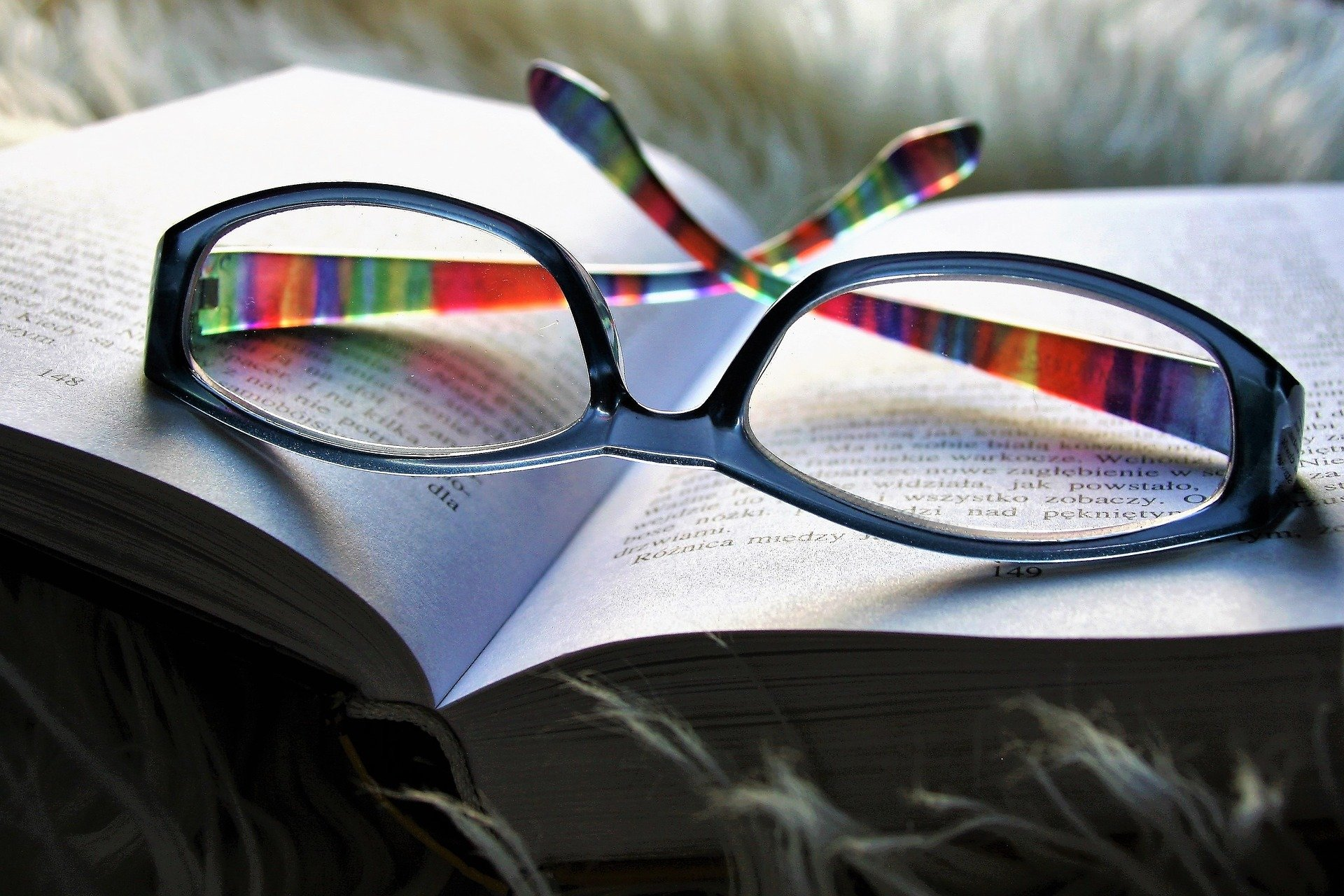 A book lies open in grass with a pair of reading glasses resting on top. The frames are blue and the arms are multi