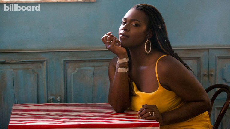 Shea Diamond, a Black woman, sits by herself at a table covered in a red striped cloth. She's wearing a yellow sundress, hoop earrings, and a bracelet. Her chin rests in her hands as she looks toward the camera from the edge of her eye. The wall behind her is a weathered blue.