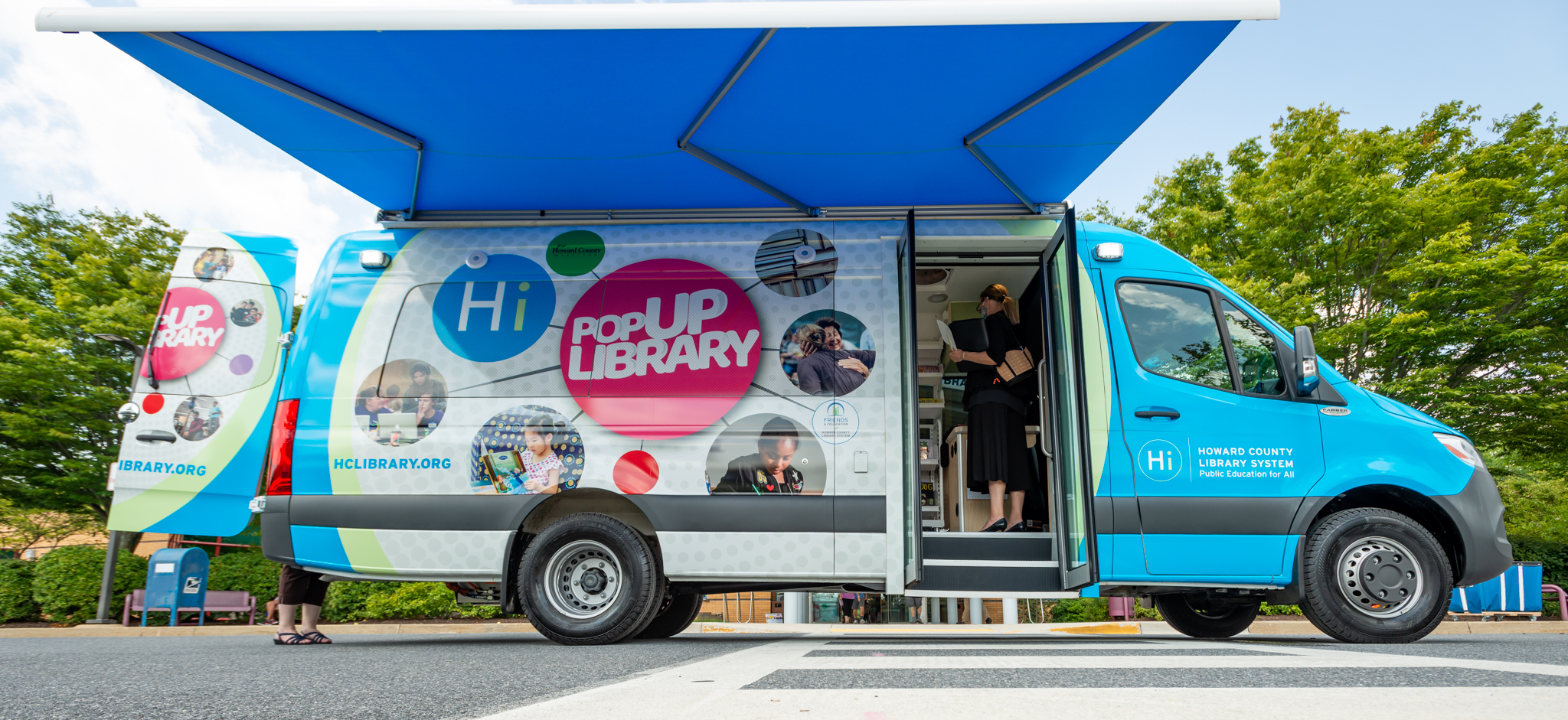 The new van, decorated with colorful circles and photos of Library events, with its awning extended.