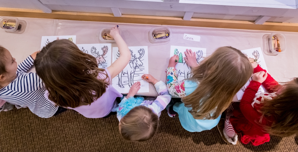 The picture shows five young children from above, at a long table coloring pictures of moose and trees. Each child has a coloring sheet and there are four containers of crayons on the table.