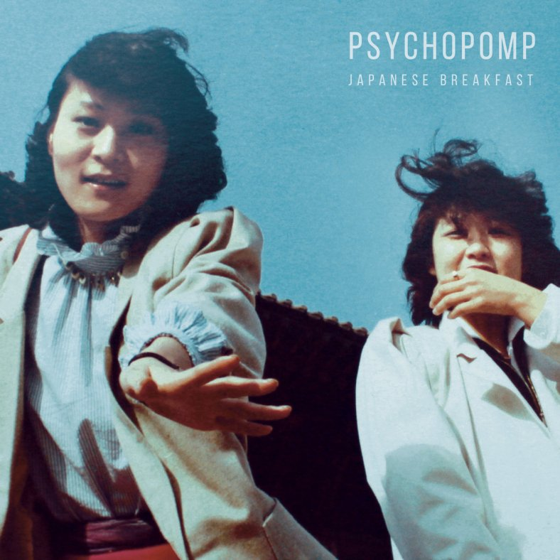 Two Asian woman look down into the camera, one reaching out. They are under a blue sky and wind is blowing their hair.