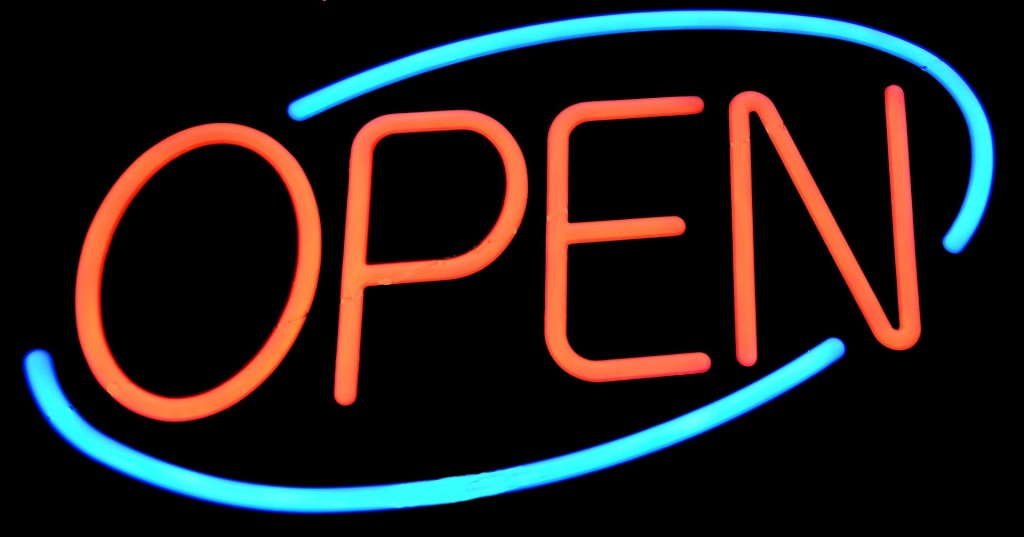 Neon sign with a bright blue oval encircling the word OPEN in red.
