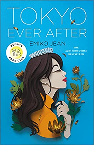 """This beautiful blue cover features the portrait of a young woman, done in paper art She has long dark wavy hair, a tiara and is surrounded by flower. The book has a sticker that says """"Reese's YA Book Club"""" and a mentions """"The New York Times Bestseller""""."""