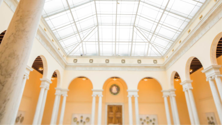 View of the atrium at the Walters Art Museum, filled with bright light, white columns, and creamy golden walls.